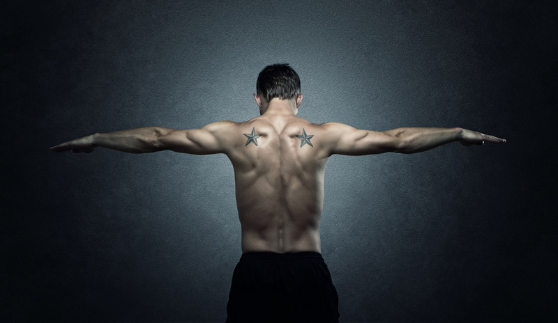 Balance, young adult stretching out arms over dark background